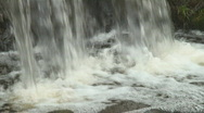 Stock Video Footage of Bottom part of a small waterfall in a city park falling down the rock