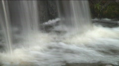 Slow-shutter panning shot of a bottom of a waterfall, smoothed water surface - stock footage