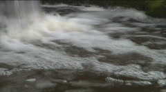Slow-shutter closeup of a bottom of a small waterfall, smoothed water surface - stock footage