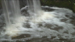 Slow-shutter panning shot of a small waterfall within rocks, smoothed water - stock footage