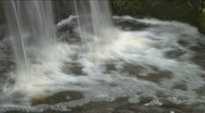 Stock Video Footage of Slow-shutter panning shot of a small waterfall within rocks, smoothed water