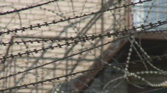 Vibrating razor wire over prison fence, shallow DOF closeup shot Stock Footage