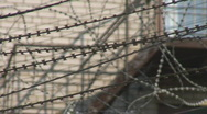 Stock Video Footage of Vibrating razor wire over prison fence, shallow DOF closeup shot
