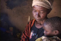 Grandmother with child by smoking fire inside mud house. - stock footage