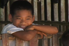 Amerindian boy smiles from the front porch of his home. Stock Footage
