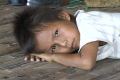 Amerindian boy takes a rest on the floor of his home Stock Footage
