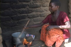 Malawi, Africa: Girl cooks over open fire Stock Footage