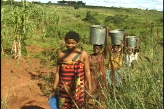 Young girls in Malawi carry water back from the creek to their homes. - stock footage
