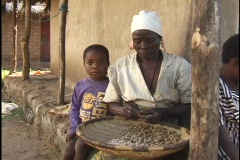 Woman and orphaned grandchildren shell groundnuts in Malawi, Africa Stock Footage