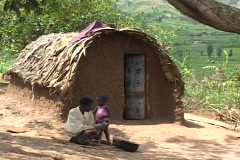 Rwanda, Africa: Woman peels potatoes in front of hut - stock footage