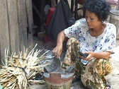Cambodia: Woman starts a charcoal fire to cook on Stock Footage