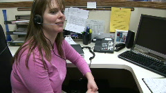 Customer Service Woman talking on telephone headset in call center at desk Stock Footage