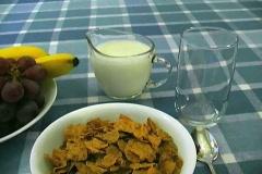 Breakfast of cereal, fruit, milk, pouring orange juice. Stock Footage