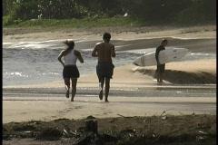 Couple jogs on beach Stock Footage
