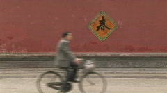 Man Rides Bike Along Red Wall in Beijing, China Stock Footage