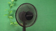 Stock Video Footage of Rotating fan on green textile wall background, close-up