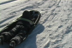 Child going down a hill on a sled Stock Footage
