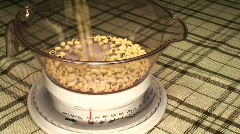 Pouring beans into bowl on scale Stock Footage