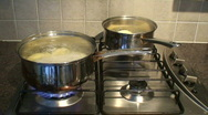 Cooking dinner on a stainless steel gas hob. HD 1080i Stock Footage
