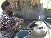 Stock Video Footage of Togo, Africa: Woman cooks over open fire  Stock Footage