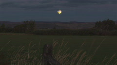 Moon at twilight over fields Stock Footage