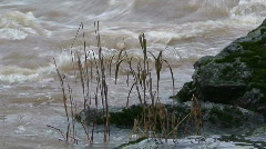 Flooded river surrounded by rock bank, close-up - stock footage