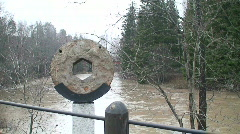Decoration from millstone near flooded river, close-up Stock Footage