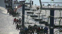Ski lift slowly transports people to the top (High Definition) Stock Footage