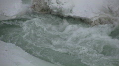 Whirlpool of icy water crashes against snowy ridge (High Definition) Stock Footage