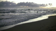 Waves gently wash up onto beach at sunrise (High Definition) - stock footage