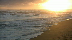 Waves gently wash up onto beach at sunrise (High Definition) Stock Footage