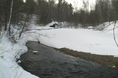 Stream flowing under ice and snow Stock Footage
