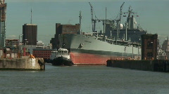 Tug pulling huge tanker into dock. HD 1080i Stock Footage