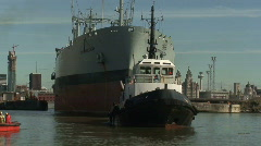 Tug pulling huge tanker into dock. HD 1080i Stock Footage
