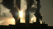 Stock Video Footage of Fumes billow from giant chimney amidt the sunlight (High Definition)