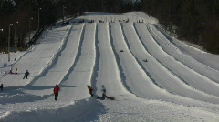 Winter scenic of people tubing down hill (High Definition, Timelapse) Stock Footage