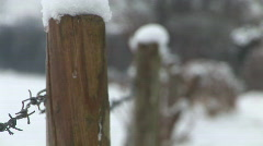 Snowy fence posts and barbed wire focus pull Stock Footage