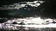Sunlight creates sparkles on the stream's flowing surface (High Definition) Stock Footage