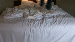 Legs and Feet of Young Boy Jumping on Bed Stock Footage