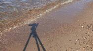 Shadow of camera on tripod on seashore sand Stock Footage