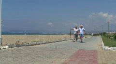 Elderly retired couple walking on beach. HD 1080i Stock Footage