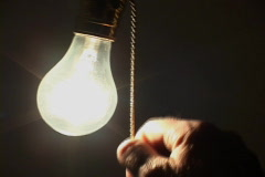 Light bulb turned on from black Stock Footage