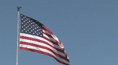 American Flag waving in the breeze against a clear blue sky - stock footage