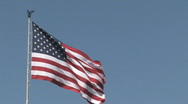 American Flag waving in the breeze against a clear blue sky Stock Footage