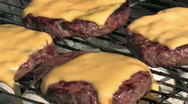 Cheeseburgers cooking on a grill     Stock Footage
