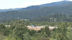 Long shot of truck traffic on Interstate highway with mountainous background Stock Footage