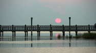 Stock Video Footage of Fishing pier boat crossing pink sunset HD
