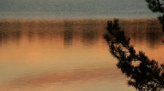 Vivid sunset over a calm lake during autumn in southern Sweden - stock footage