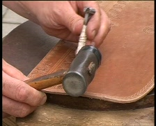 Handcraftsman tanned leather handcraft perforation in progress, PAL Stock Footage