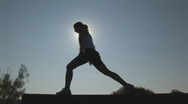 Woman stretching at sunset - low lunge Stock Footage